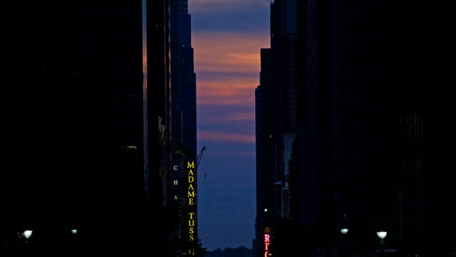 epa04774885 The sun is seen setting behind buildings on 42nd Street during the Manhattanhenge, a twice a year occurrence in which the setting sun aligns with the street grid of New York City, in Manhattan, New York , USA, 29 May 2015. This year the sun was mostly obscured by low-level clouds. EPA/PETER FOLEY