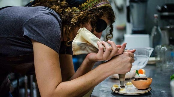 Hannah Ellaham, owner of Mortar & Pestle, puts the final touches on one of her culinary confections.