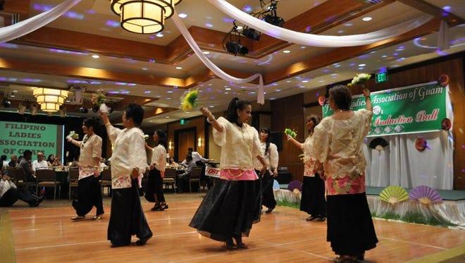 """Members of Filipino Ladies Association of Guam perform a cultural dance called """"Lawiswis Kawayan."""""""