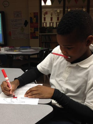 J.I. Barron Sr. Elementary fifth-grader Jermaine McNeal works on an activity about Socktober, a global sock drive movement that the school is participating in this month.