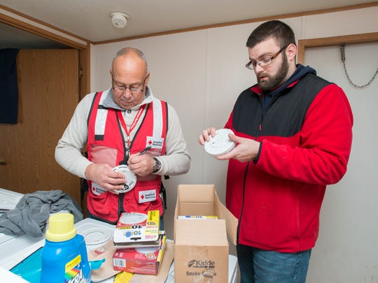 Red Cross volunteers Manny Sanchez, left, and Christian Smith install new smoke detectors in Farron Keith Jackson's home in Pensacola on Monday, January 15, 2018.