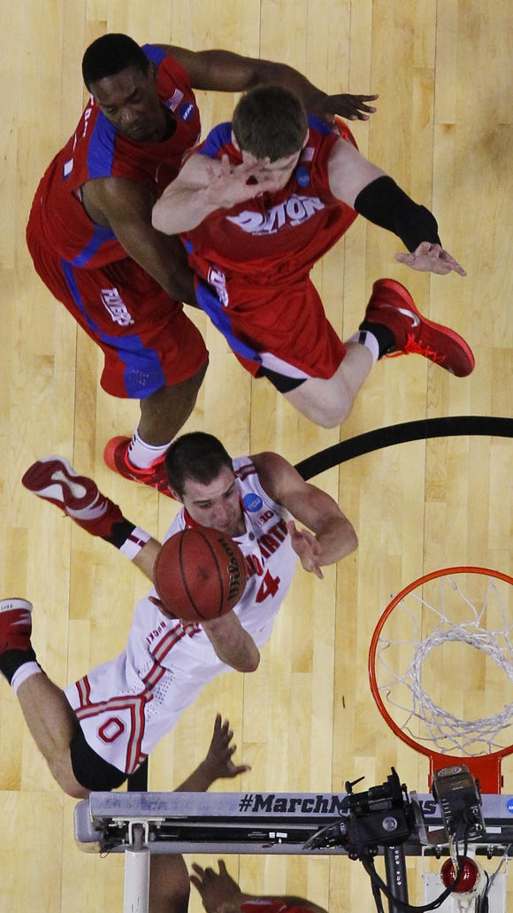 Ohio State's Aaron Craft (4) drives to the basket against Dayton's Dyshawn Pierre (21) and Matt Kavanugh (35) during the first half of a second-round game in the NCAA college basketball tournament in Buffalo, N.Y., Thursday, March 20, 2014. (AP Photo/Bill Wippert)