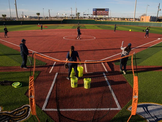Carroll softball players field balls during practice