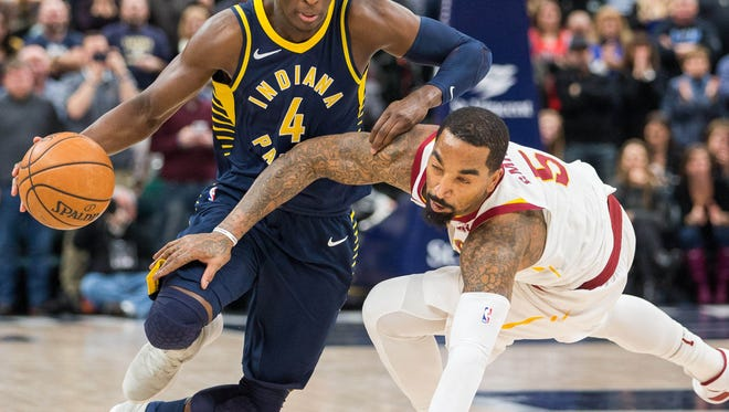 Jan 12, 2018; Indianapolis, IN, USA; Indiana Pacers guard Victor Oladipo (4) dribbles the ball past a diving Cleveland Cavaliers guard JR Smith (5) in the second half at Bankers Life Fieldhouse. Mandatory Credit: Trevor Ruszkowski-USA TODAY Sports