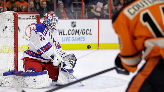 New York Rangers' Cam Talbot, left, blocks a shot by Philadelphia Flyers' Sean Couturier (14) during the second period Friday in Philadelphia.