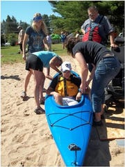 Carrie Butt, owner of Dive Point Scuba, and Shirley Orr, a nurse with Midstate Independent Living, help participant Luke Widowski into a kayak.
