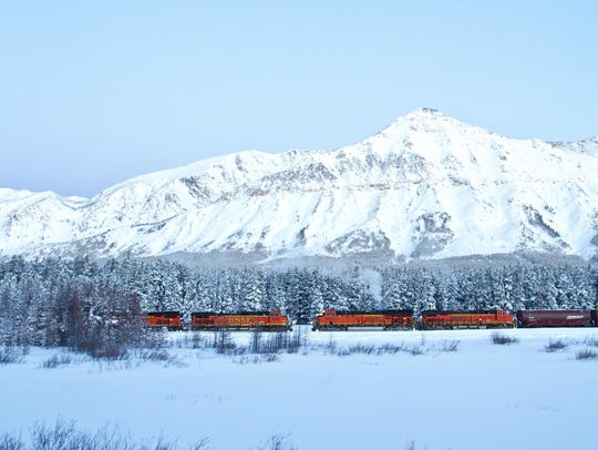 The train travels over the snowy landscape near the