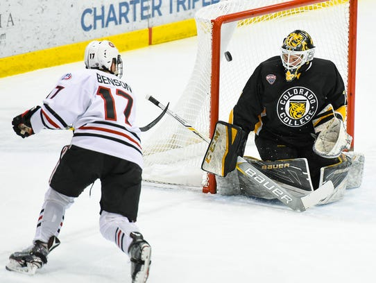 St. Cloud State's Jacob Benson, 17, puts the puck over