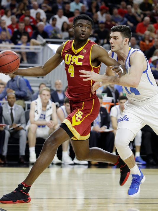 Southern California's Chimezie Metu passes around UCLA's Gyorgy Goloman during the first half of an NCAA college basketball game in the quarterfinals of the Pac-12 men's tournament Thursday, March 9, 2017, in Las Vegas. (AP Photo/John Locher)
