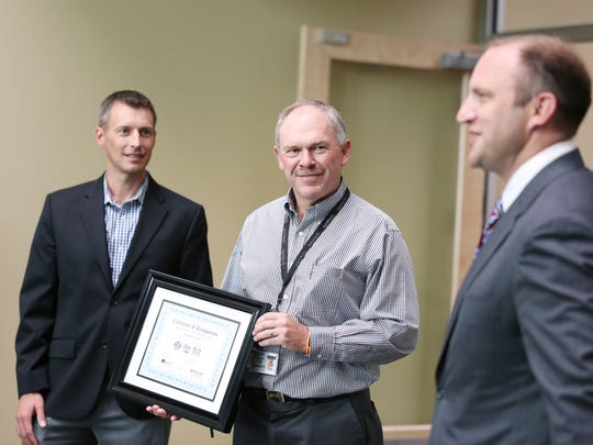 Chad Summers, left, AKT Manufacturing Business Advisor, and SEDCOR President Chad Freeman present Steve VanArsdale, center, General Manager of Garmin AT, with a certificate of recognition in honor of Manufacturing Day Thursday, Oct. 1, 2015, during a presentation at Garmin AT in Salem, Ore.