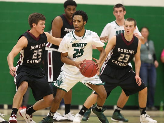 North guard Neico Greene handles the ball while being guarded by Dowling Catholic's Eric Fardal (25) and Nick McMurray (23) during a high school basketball game on Friday, Jan. 9, 2015, at North High School in Des Moines, Iowa.