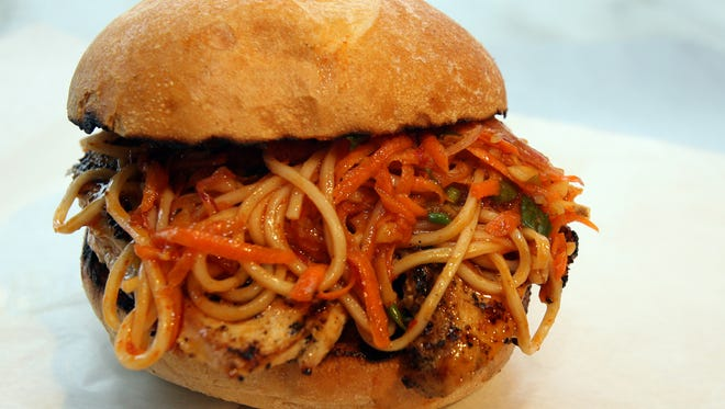 Sourdough roll with marinated grilled chicken, spicy lo mein noodles, ginger carrot slaw and house-made ponzu sauce at Melt Sandwich Shop in White Plains.