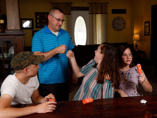 Eric DeVoe bumps fists with his oldest daughter Peighton