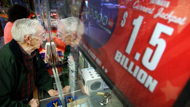 Tony Floyd passes his money through the window Jan. 12, 2016, while purchasing a Powerball ticket at the Elvis Presley BP near the Alabama-Tennessee state line in Memphis. The convenience store is said to be the busiest lottery location in Shelby County.