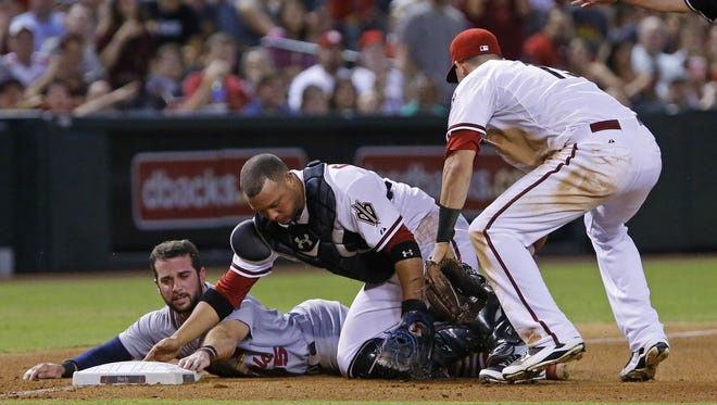 St. Louis Cardinals baserunner Greg Garcia slides safely into third base as Arizona Diamondbacks catcher Welington Castillo tries to tag him out in the sixth inning on Monday, Aug. 24, 2015, in Phoenix.