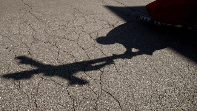 The shadow of a priest holding a crucifix is cast on the ground as he leads the Via Crucis, or Way of the Cross ceremony, at the Ospedale di Circolo in Varese, Italy.