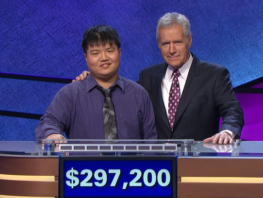 "This image released by Jeopardy Productions, Inc. shows host Alex Trebek with contestant Arthur Chu in front of a total of his winnings at a taping of ""Jeopardy,"" in Culver City, Calif. Chu, who won big money while taking heat for his renegade style, has been defeated. Chu finished in third place with zero dollars on the Wednesday, March 12, 2014, edition of the syndicated quiz show. He had reigned for 12 days. His total winnings were $297,200. (AP Photo/Jeopardy Productions, Inc.)"
