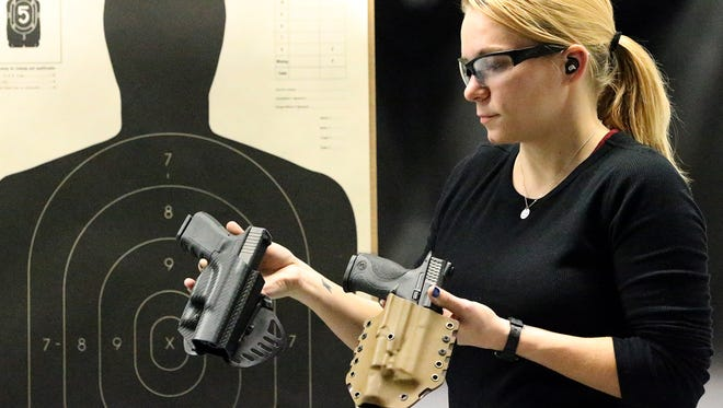 Alexandra Wilson, marketing director and firearms instructor at Sportsman's Elite indoor shooting range and pro shop at 4520 Doniphan, shows two varieties of handgun holders Tuesday. The holster at right attaches to a sturdy belt while the black one at left has a paddlelike tab that slips inside a pair of pants at the waist. Both types are made of a strong plastic material called Kydex, Wilson said.