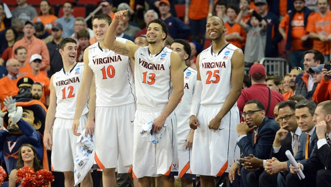 The Virginia Cavaliers bench celebrates against against the Memphis Tigers during the second half of a men's college basketball game during the third round of the 2014 NCAA Tournament at PNC Arena.