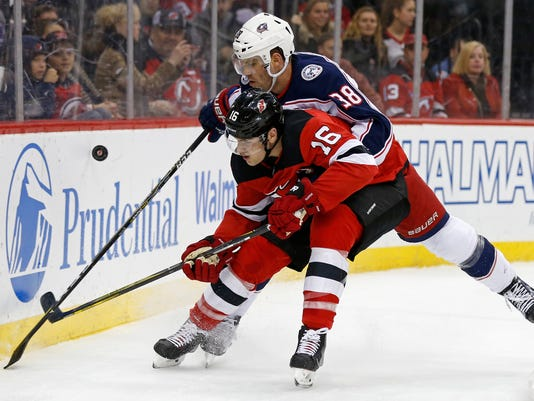 New Jersey Devils defenseman Steven Santini (16) battles for the puck with Columbus Blue Jackets center Boone Jenner (38) during the first period of an NHL hockey game, Friday, Dec. 8, 2017, in Newark, N.J. (AP Photo/Adam Hunger)