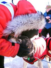 Kristin holding Miyuki, one of her dogs, after finishing the Iditarod.