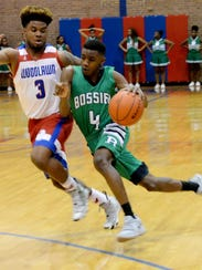 Bossier's Kaalas Roots drives against Woodlawn's Larry Moton Tuesday night at Woodlawn.