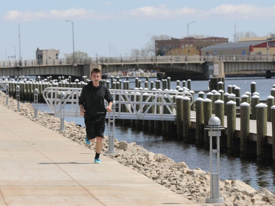 Cameron Buelow runs on part of Oshkosh's river walk in front of The Rivers Senior Living Apartments. Gov. Scott Walker's proposed budget calls for the elimination of Knowles-Nelson Stewardship funds. The city has relied heavily on these funds for construction of the river walk, receiving $1.7 million for the three segments that have been built already.