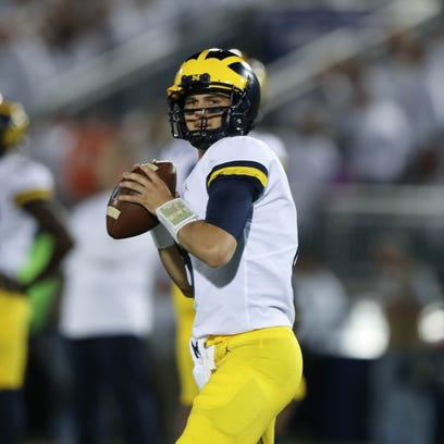 Michigan's John O'Korn warms up before action against