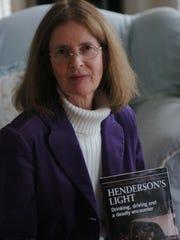 "Nancy Henderson with a copy of ""Henderson's Light."""