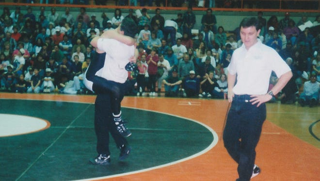 Herb Stinson, left, embraces his son, Jeremy, after the teenager won his second individual state title at the 1994 state wrestling tournament at Lillywhite Gym in Aztec.