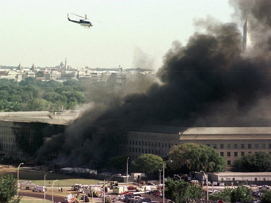 A helicopter flies over the burning Pentagon.