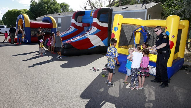 Chase McDonald, a reserve officer with the Bloomfield Police Department, opens the bounce house for kids taking part in Summer Jam, a block party put on by the department's Police Athletic League, on July 22, 2016, at the Enchantment Village mobile home park in Bloomfield.