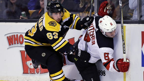 Boston Bruins left wing Brad Marchand (63) checks New