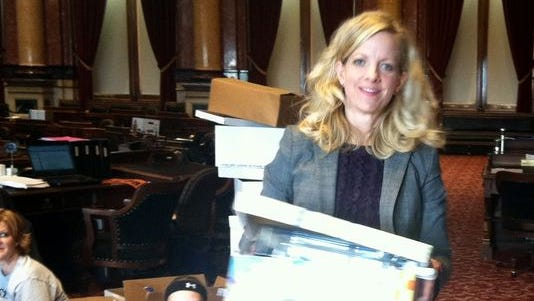 State Sen. Janet Petersen, D-Des Moines, hauls her paperwork out of the Iowa Senate chamber past a group of young people touring the Capitol in early May. The new state laws she and her fellow lawmakers passed go into effect Tuesday.