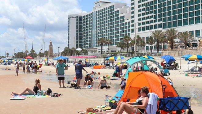 Visitors play on the beach in front of the Hilton Daytona Beach Oceanfront Resort on Tuesday. A combination of coronavirus news and rainy weather yielded a disappointing July 4th holiday weekend for many Volusia County hoteliers.