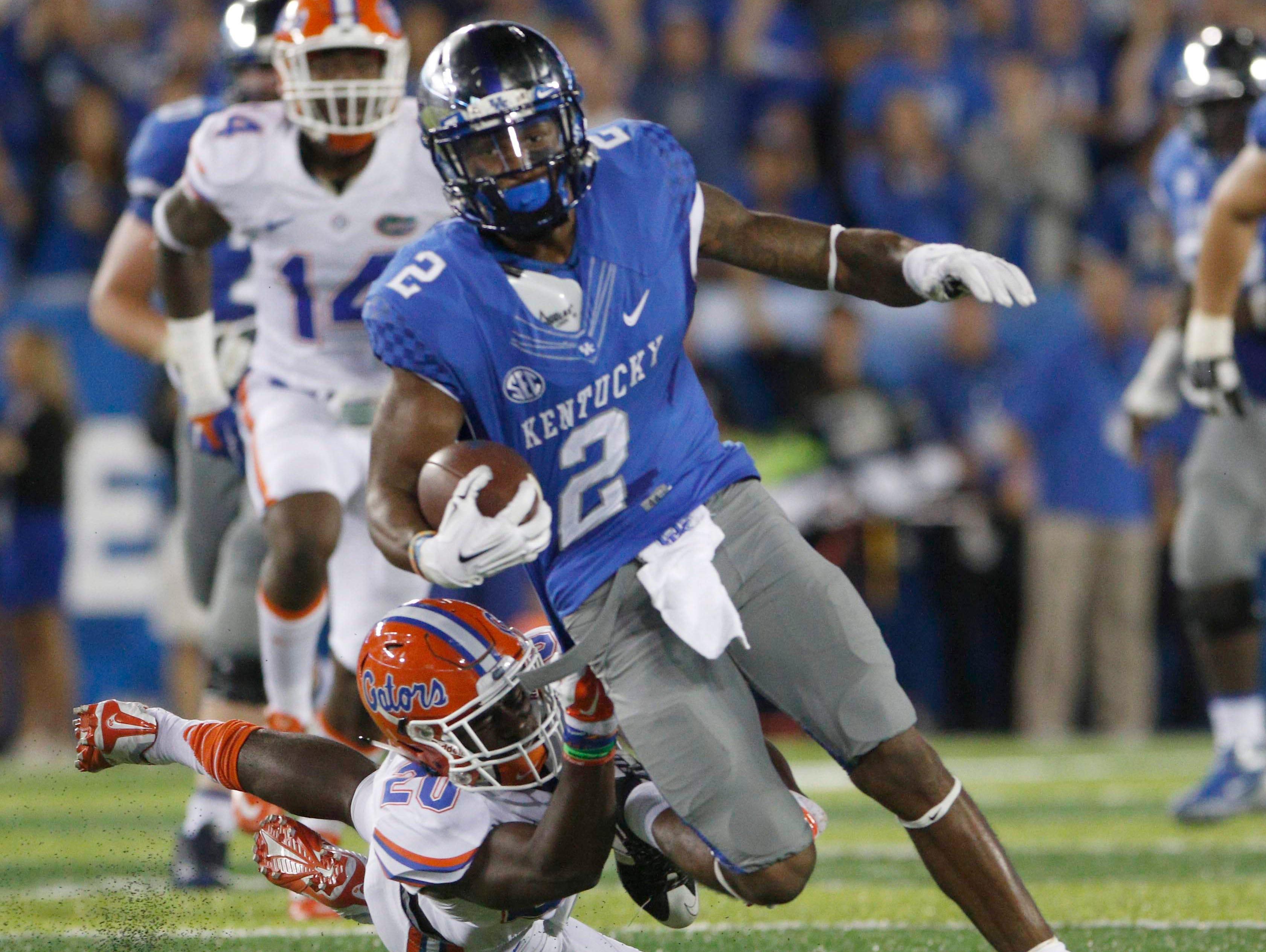 Sep 19, 2015; Lexington, KY, USA; Kentucky Wildcats wide receiver Dorian Baker (2) runs the ball against Florida Gators defensive back Marcus Maye (20) during the game at Commonwealth Stadium. Florida defeated Kentucky 14-9.