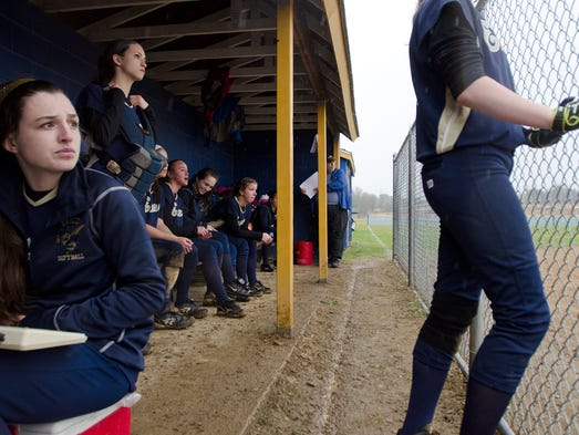 Essex's Jackie Littlefield, left, is sheltered from the rain alongside her teammates in the dugout while Essex is at bat against Rice at Tuesday's game at Essex on April 22, 2014. The game was later cut short for a rain delay.
