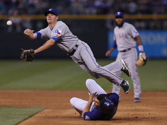 Texas Rangers second baseman Josh Wilson, top, flies