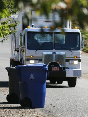 Calvin Coats, of D&O Garbage and Recycling, dumps blue recycling bins into his truck in rural south Salem.