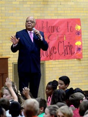 Ingham County District Court Judge Hugh Clarke Jr., who served several years on the Lansing Board of Education, talks with children in a Holt school.
