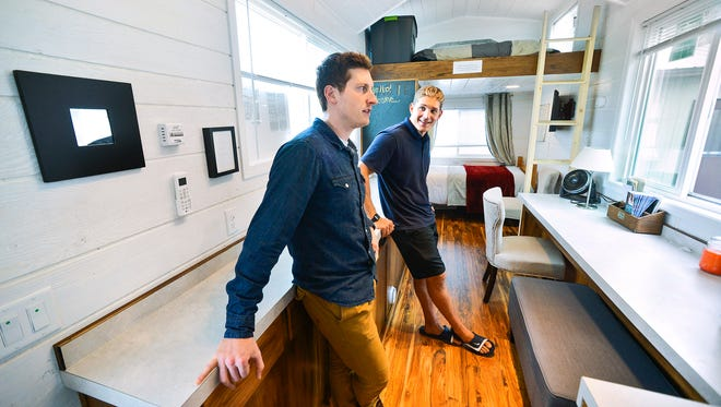 "NextDoor Housing founders John Louiselle, left, and Jesse Lammi explain on Aug. 12 some of the amenities and features of the ""granny pods"" they sell in Big Lake. This one, an air-conditioned 32-by-8-footer, is the largest they sell. It has a small bedroom, a handicap-accessible bathroom, a kitchen without a stove, a sink and a bunk for a caregiver. The ladder is for a caregiver to use to access the bunk."