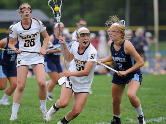 Moorestown's Quinn Nicolai moves the ball by Shawnee's