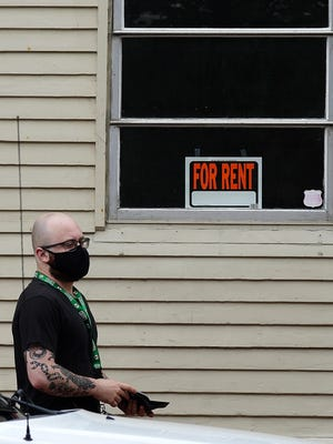 """A man walks by a """"For Rent"""" sign posted in Portsmouth last summer. The federal moratorium on evictions implemented by the Center for Disease Control ends this Saturday, July 31."""