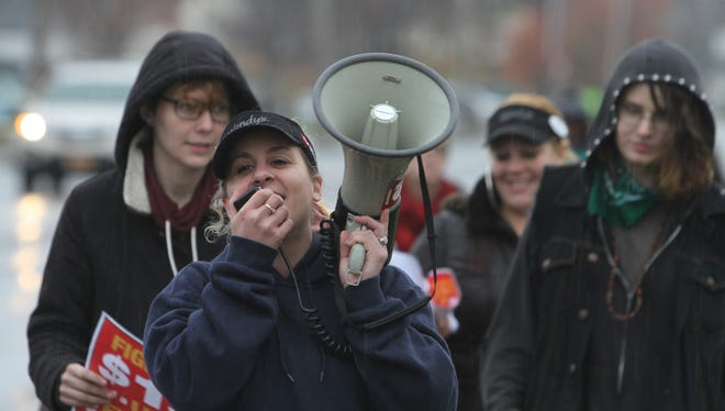 Erika Peterson, who works at a Wendy's Restaurant, announces over the megaphone, the location of the march later in the day as the workers leave.