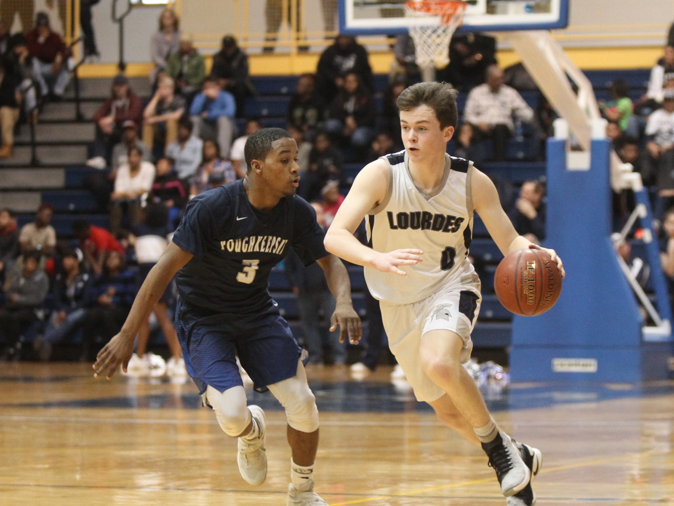 Lourdes' Brady Hildebrand dribbles up court against Poughkeepsie's Mo'Quez Dickens during the Class A regional final on March 11, 2017.