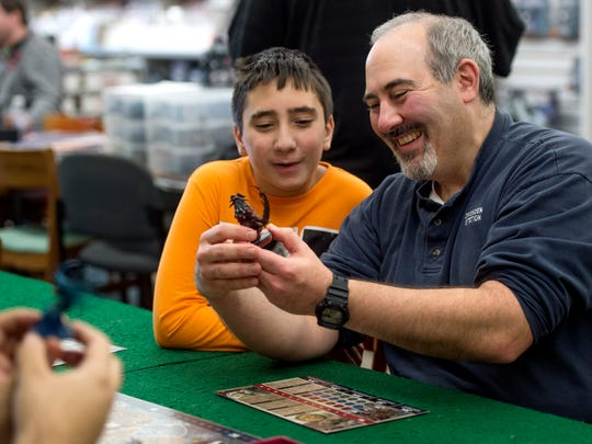 Mike Tiberi and his son Nick, 12, look at a hand-painted Fire Giant miniature from the game Blood Rage at Knight's Comics & Games in Henderson, Ky., on Saturday, Nov. 11, 2017. Tiberi lives in Newburgh, and has been coming to the store to play Warhammer 40,000 and other games since he learned of its existence. He started teaching his son how to play Warhammer 40,000 last year.