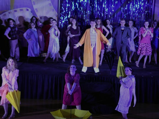 "Don Lockwood (Grant Trivette), center, performs the iconic number ""Singin' in the Rain"" during a Powell Middle School production of the junior version."
