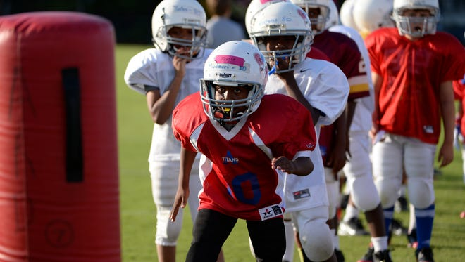 Kids participate in a Heads Up Football drill at Fairfax County Youth Football practice.