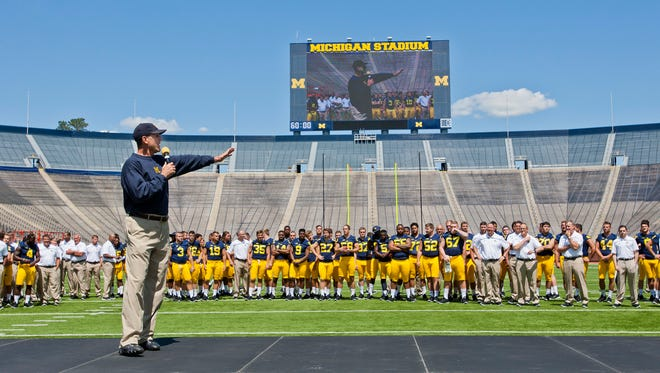 Michigan head coach Jim Harbaugh introduces his team to fans and media at Michigan Stadium, during the NCAA college football team's annual media day in Ann Arbor, Mich.,
