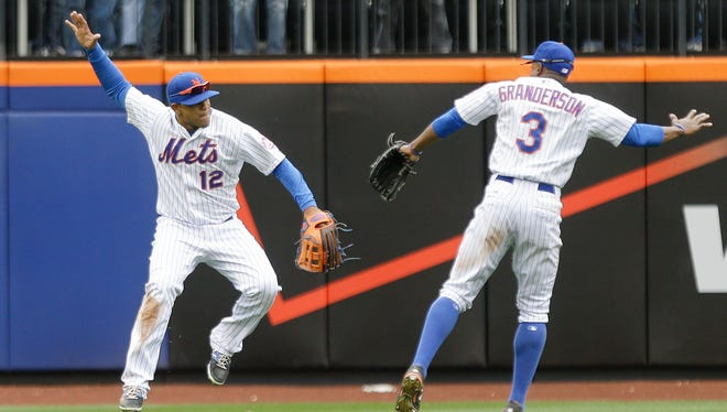 New York Mets' Juan Lagares (12) and Curtis Granderson (3) celebrate after their 6-3 win over the Atlanta Braves in a baseball game Thursday, April 23, 2015, in New York.